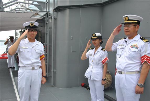 Miembros de la tripulación de uno de los buques saludan a los visitantes