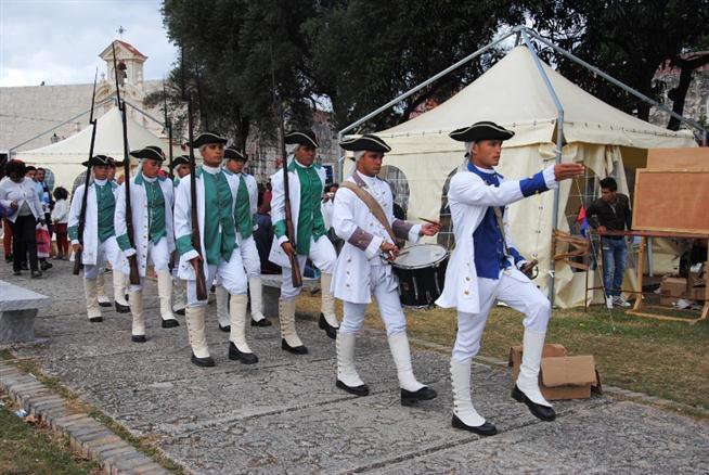 Soldados españoles van comandados por oficial jefe hacia la Plaza de Armas, en San Carlos de la Cabaña.
