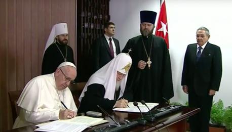 El Papa y el Patriarca sentados a la mesa firman la declaración conjunta, en presencia de Raúl Castro. Foto: Cubadebate