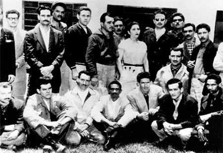 """Fidel Castro (de pie, cuarto de derecha a izquierda con lentes) en 1955, en México, donde conoció a Ernesto """"Che"""" Guevara (sentado, segundo de izquierda a derecha). La foto fue tomada en la casa de María Antonia González, punto de reunión de los recién llegados de la isla, y cuartel general del Movimiento 26 de Julio."""