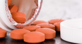 an-open-medication-container-spilling-ibuprofen-tablets-out-onto-a-table-16X9