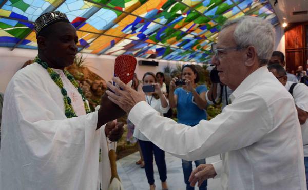 Juan Martel, presidente de la filial santiaguera de la Sociedad Yoruba de Cuba (I), entrega la Mpaka del Premio Internacional Casa del Caribe, al Dr. Eusebio Leal Spengler, Historiador de La Habana, en ceremonia celebrada en el Salón de los Vitrales de la Plaza de la Revolución de Santiago de Cuba, el 6 de julio de 2018. ACN FOTO/Miguel RUBIERA JÚSTIZ/ogm
