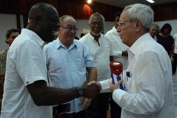 El artista de la plástica Eduardo Roca (I), felicita al Dr. Eusebio Leal Spengler, Historiador de La Habana, después de recibir la Mpaka y el certificado de Premio Internacional del Caribe, en ceremonia celebrada en el Salón de los Vitrales de la Plaza de la Revolución de Santiago de Cuba, el 6 de julio de 2018. ACN FOTO/Miguel RUBIERA JÚSTIZ/ogm