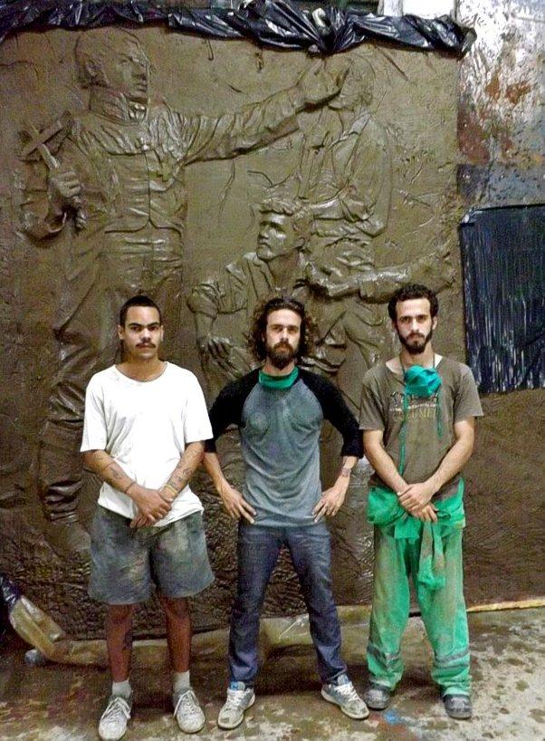 De izquierda a derecha, Mario Velázquez Triana, José Carlos Beltrán Labrada y su hermano Pedro Enrique frente a una parte de lo que será el mural que recoge el momento de fundación de la Colonia de Fernandina de Jagua. / Foto: Igorra