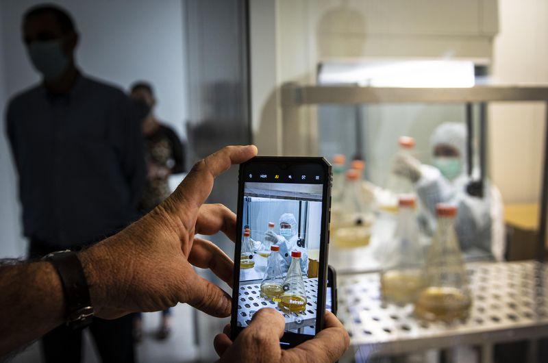 Un periodista toma una foto con un teléfono celular de un científico que trabaja en el desarrollo de Abdala, una vacuna experimental para el COVID-19 en el Centro de Ingeniería Genética y Biotecnología (CIGB) en La Habana, Cuba, el jueves 25 de febrero de 2021. (Ramon Espinosa/AP)