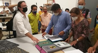 José Adrián Vitier explica a Dulce María Buergo y Michael Gonzales proyecto de encuadernación de libros de Vitier